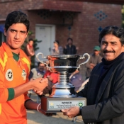 Lahore Ravi Under-19s captain receives the winning trophy from Javed Miandad