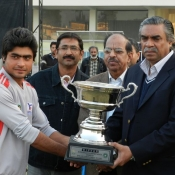Sialkot U-19 team skipper receiving winnings trophy from PCB Governing Board Shakil Shaikh